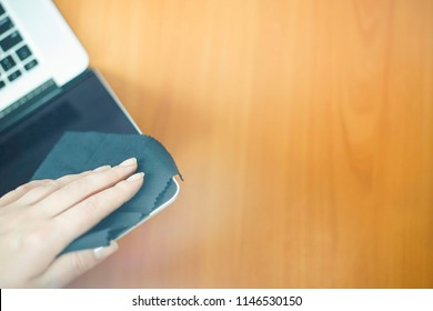 Close up of woman hands cleaning laptop screen with black rag. top view with copy space for text