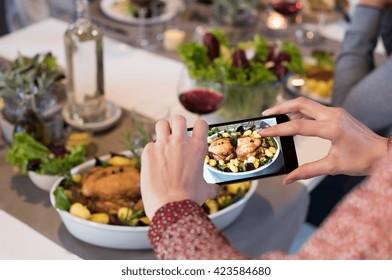关闭女人的手点击食物的图片。 女人使用智能手机食品摄影. 用智能手机拍摄烤韭菜的照片特写女手。