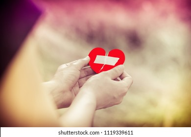 Close up woman hands connecting torn pieces of hart,Female hands holding broken heart,hearten concept,Hope concept.