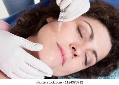 Close up woman hands of cosmetologist making hyaluronic injection in female face