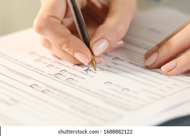 Close up of woman hands filling form crossing yes checkbox on a desk