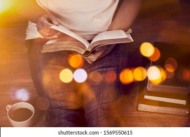 Close up of woman hands hold and reading bible indoor near a cup of coffee and book stack with window light and Bokeh, Christian background