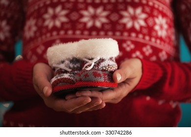 Close Up Of Woman Hands Holding Baby Christmas Shoes