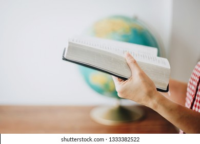 Close up of woman hands holding bible over blurred world globe on wooden table with white wall background, christian mission concept, Copy space