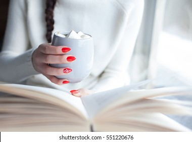 Close up of woman hands holding a book and a cup of coffee with marshmallows. Red nails winter nail art and student home education concept