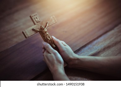 Close up of woman hands holding crucifix of Jesus Christ while praying to God on wooden table background, Christian trust and faith concept with copy space.