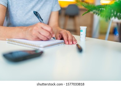 Close up of woman hands holding Glucose meter and use pen to write schedule check blood sugar level to planner notbook with lancet. Use as Medicine, diabetes, glycemia, health care and people concept.