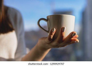 Close up of a woman hands holding a hot coffee cup in winter near a window at home with outdoors in the background