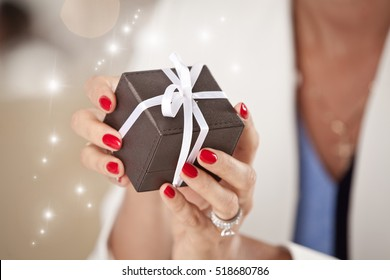 Close up of woman hands holding small gift with ribbon. Holidays and celebrations concept