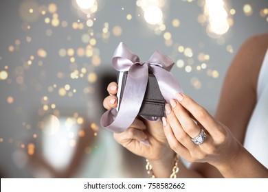 Close up of woman hands holding small gift with ribbon. Holidays and celebration concept. Christmas background