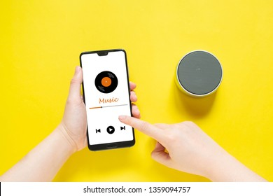 Close up of woman hands holding smartphone with music media player application and connect wireless bluetooth speaker portable on yellow color background. Technology concept.