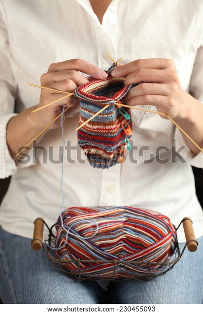 close up of woman hands knitting with knitting needles and yarn ball