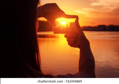 Close up of woman hands making frame gesture with sunset. Future planning, Silhouette and sunlight outdoor.
