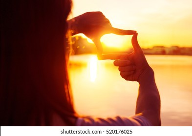 Close up of woman hands making frame gesture with sunset, Female capturing the sunrise, Future planning, sunlight outdoor.