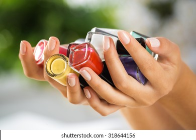 Close up of woman hands with nail polishes of different colors