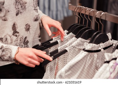 Close up woman hands on clothes hangers in a store buying clothes.Shopping.Woman looking for suitable size