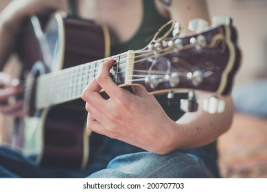 close up of woman hands playing guitar at home