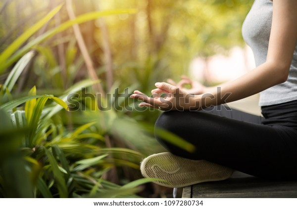 Close up woman hands practicing yoga and meditation in the lotus position at the forest.