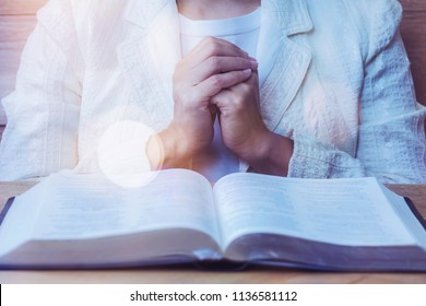 close up of woman hands praying to God while reading bible on wooden table  in morning devotion, Christian