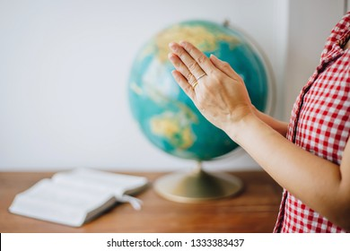 Close up of woman hands praying over blurred world globe and bible on wooden table with white wall background, christian world mission concept, Copy space