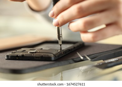 Close up of woman hands removing screws on a smart phone on a desk