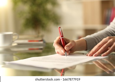 Close up of woman hands signing document with pen on a desk at home