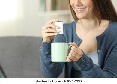 Close up of a woman hands throwing sacharine pill into a mug sitting on a couch in the living room at home