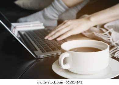 Close up of a woman hands typing a laptop for shopping online with morning coffee at home.