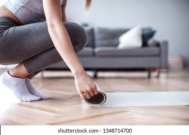 Close up woman hands unrolling mat is preparing for fitness workout in living room at home. Yoga matt.