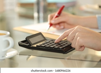 Close up of woman hands using calculator and writing on a document on a desk at home