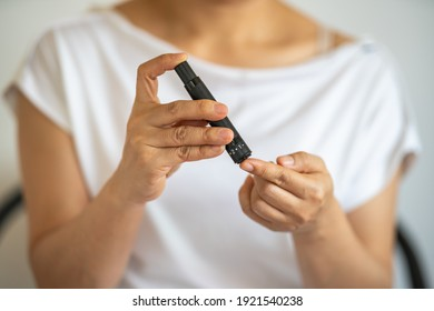 Close up of woman hands using lancet on finger to check blood sugar level by Glucose meter. Use as Medicine, diabetes, glycemia, health care and people concept.