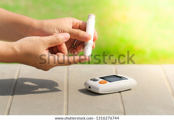 Close up woman hands using lancet on finger to check blood sugar level by Glucose meter, Healthcare Medical Check up, Medicine, diabetes, hyperglycemia concept