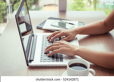 Close Up of woman hands using mobile phone and laptop computer with blank copy space screen for your advertising text message or content business in the Vintage effect.