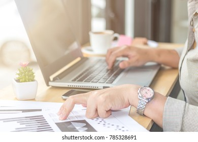 Close Up of woman hands using mobile phone and laptop computer with blank copy space screen for your advertising text message or content business at a coffee shop with a document.