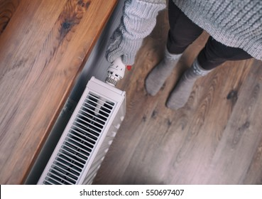 Close up of woman hands wearing woolen gloves turning heater up. Snow at the windowsill. Winter energy saving concept.