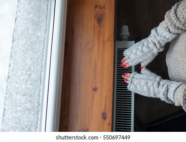 Close up of woman hands wearing woolen gloves warming up over a radiator. Snow at the windowsill. Winter energy saving concept.