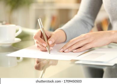 Close up of woman hands writing a letter sitting on a desk at home