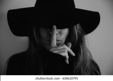 Close up of a woman in a hat with face covered by hat, implying hushing with her finger in dark noir black and white tones.