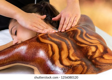 Close up of woman having hot antioxidants chocolate back massage. Beautician rubbing dark cacao wax on skin.