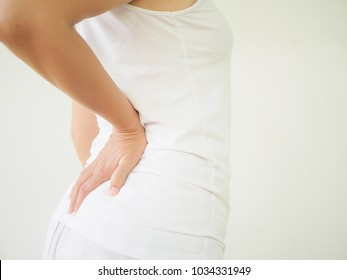 Close up woman having pain in injured back. Health care and back pain concept.