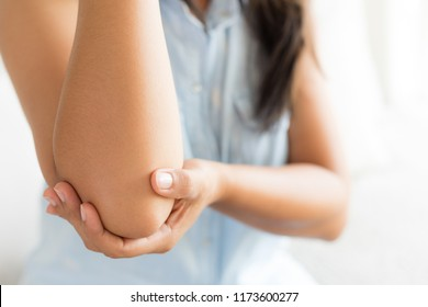 Close up woman having pain in injured elbow. Health care and arm pain concept.