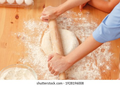 Close up of woman with her child kneading dough