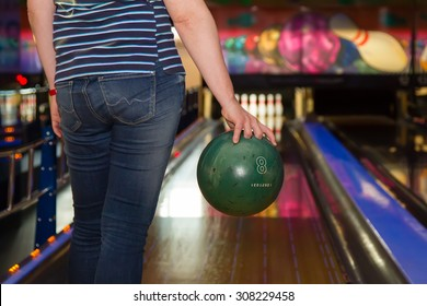 Close up of woman holding a bowling ball at the bowling club, rear view