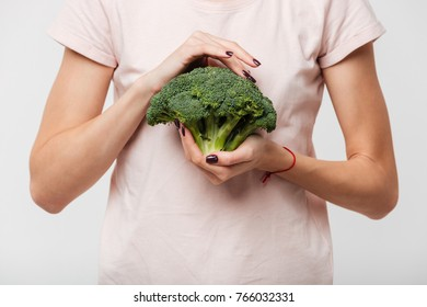 Close up of a woman holding broccoli isolated over white background