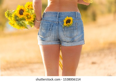 Close up of a woman holding a bunch of sunflowers and one sunflower in her jeans pocket on a warm sunny day