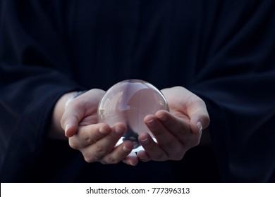 Close up of a woman holding a glass ball in her hand.