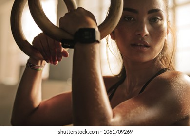 Close up of woman holding gymnastic rings at the gym and looking at camera. Fitness woman looking tired after intense  workout.