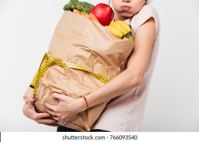 Close up of a woman holding heavy bag with groceries wrapped with a measuring tape isolated over white background