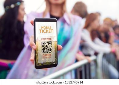 Close Up Of Woman Holding Mobile Ticket On Screen To Camera As She Arrives At Entrance To Music Festival