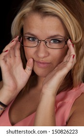 A close up of a woman holding on to her glasses with a serious expression on her face.